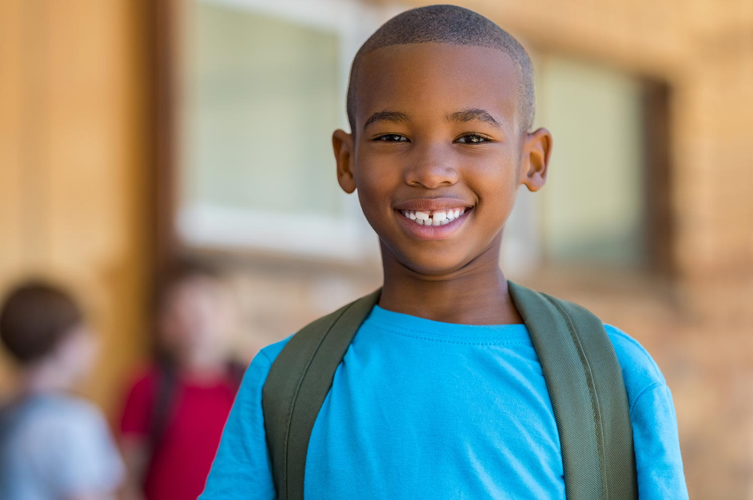 A small boy in a bright, blue shirt smiles widely to show off his white teeth.
