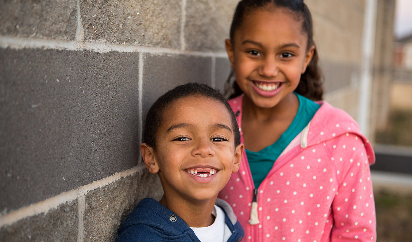 Two young dental patients smile proudly to show off their healthy teeth.